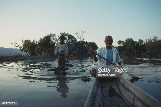 Maung Oo a boatman on Inle Lake in Burma February 1988 To the left is a boy riding a swimming water buffalo