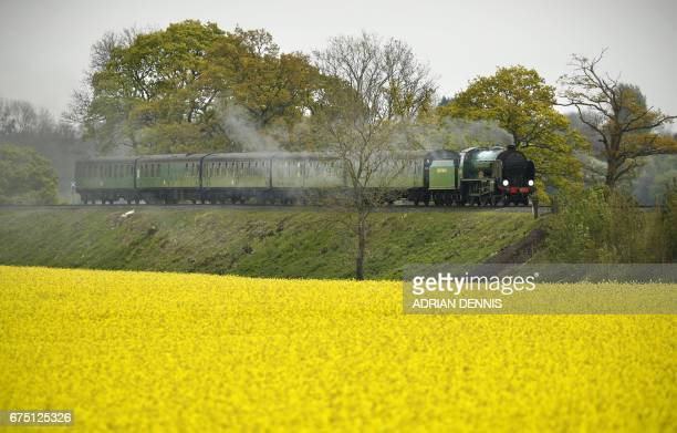A Maunsell 440 Express passenger locomotive travels along The Watercress Line alongside a rape seed crop near Alton in Hampshire on April 30 2017 The...