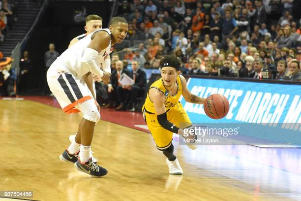 J Maura of the UMBC Retrievers dribbles the ball around Devon Hall of the Virginia Cavaliers during the first round of the 2018 NCAA Men's Basketball...