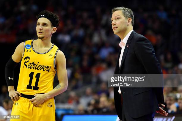 J Maura of the UMBC Retrievers stands with head coach Ryan Odom on the sideline during their game against the Virginia Cavaliers during the first...