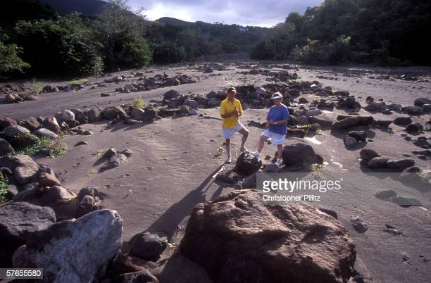 Maureen and David Hodd local expat residents of 35 years standing on the island pictured amidst the ruins and mud flow rocks and ash of Monserrats's...