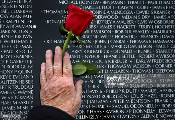 Maureen Cabral of Winchester holds a rose up to the name of her husband John J Cabral who was killed in action in Vietnam in 1972 on a panel of the...