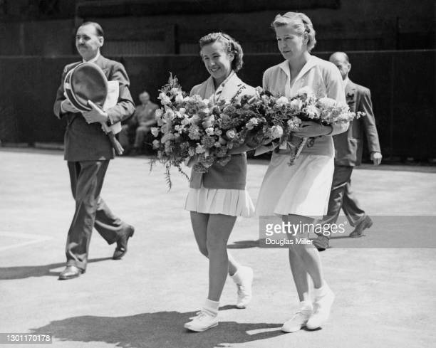 Maureen Connolly of the United States and compatriot Louise Brough walk on to Centre Court carrying bouquets of flowers before their Women's Singles...