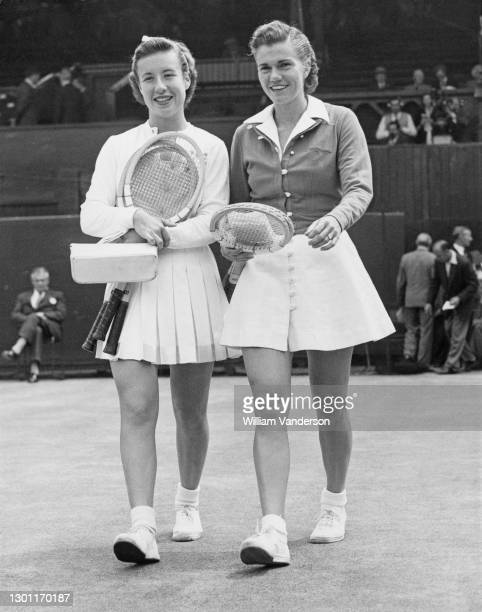 Maureen Connolly of the United States and compatriot Shirley Fry walk on to Centre Court before their Women's Singles Semi Final match at the...