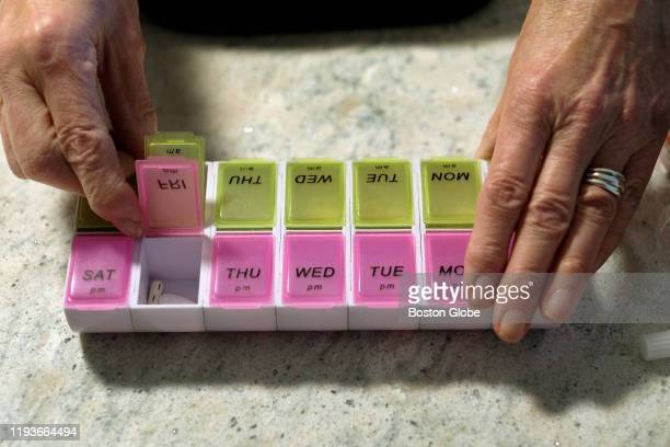 Maureen Dixon displays her pills organizer that she uses to keep track of the prescription drugs vitamins insulin and arthritis injections she takes...