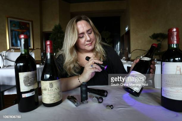 Maureen Downey fake wine expert uses a blue light to check the capsule and cork and used to see the age of the paper used in the label on a bottle of...