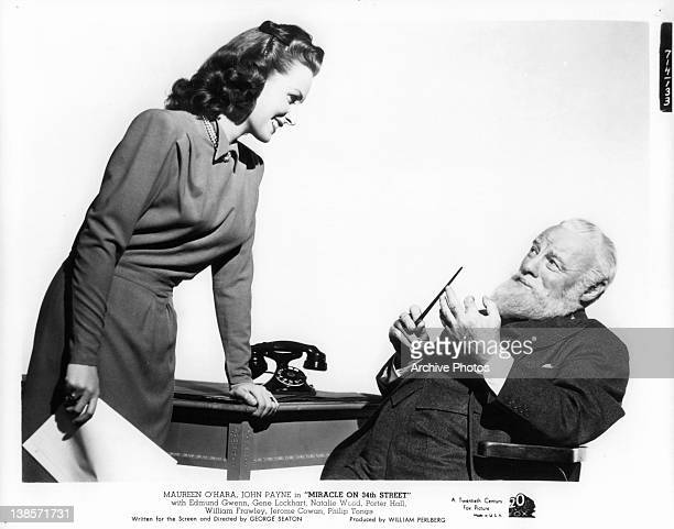 Maureen O'Hara bending down talking with Edmund Gwenn sitting in a chair who has a full beard in a scene from the film 'Miracle On 34th Street' 1947