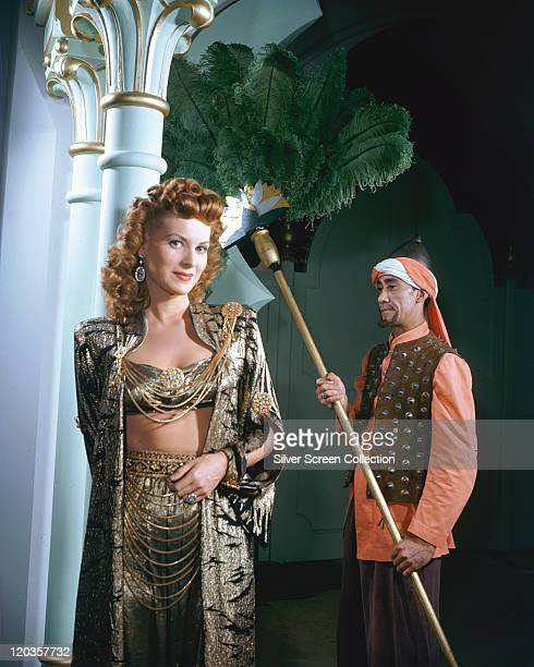 Maureen O'Hara Irish actress alongside an attendant holding a large feather fan in a publicity portrait issued for the film 'Sinbad the Sailor' 1947...