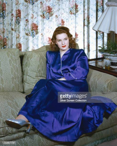 Maureen O'Hara Irish actress wearing a long blue silk dressing gown while reclining on a grey sofa circa 1950