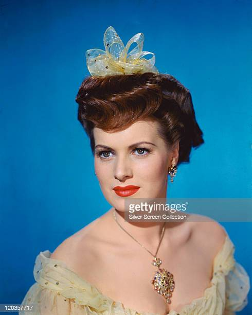 Maureen O'Hara Irish actress wearing a pale green strapless yellow dress and matching hair ornament with a large jewelled pendant hanging from a gold...