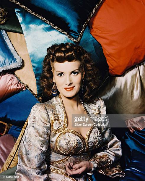 Maureen O'Hara Irish actress weraing a silk jacket with gold brocade while posing in front of silk cushions in a variety of colours in a studio...