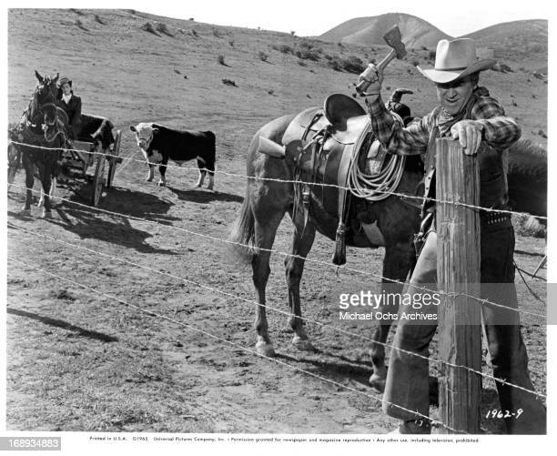 Maureen O'Hara watches James Stewart chop through barbed wire blocking their way to Texas in a scene from the film 'The Rare Breed' 1966