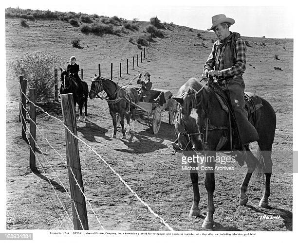 Maureen O'Hara watches James Stewart figure out how they are getting through the wire blocking their way to Texas in a scene from the film 'The Rare...