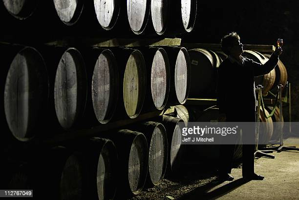Maureen Stronach, an employee at Diageo's Dalwhinnie distillery views whisky drawn from a cask in the store room on April 21, 2011 in Dalwhinnie,...