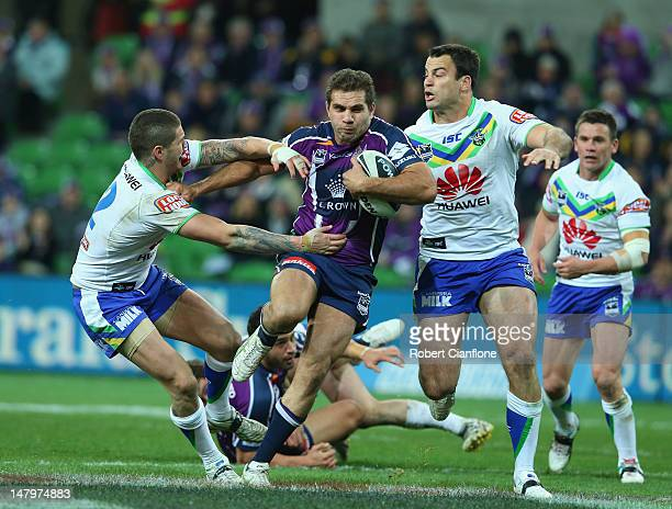 Maurice Blair of the Storm is challenged by Sandor Earl and David Shillington of the Raiders during the round 18 NRL match between the Melbourne...