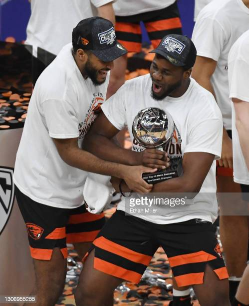 Maurice Calloo and Rodrigue Andela of the Oregon State Beavers celebrate with the trophy after their 70-68 victory over the Colorado Buffaloes to win...
