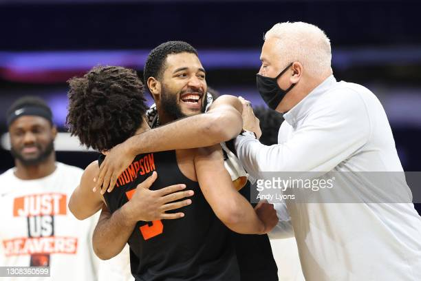 Maurice Calloo and Ethan Thompson of the Oregon State Beavers celebrate their 80-70 win with their head coach Wayne Tinkle over the Oklahoma State...