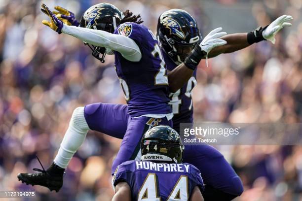 Maurice Canady of the Baltimore Ravens celebrates with Chris Board and Marlon Humphrey after intercepting a pass against the Cleveland Browns during...