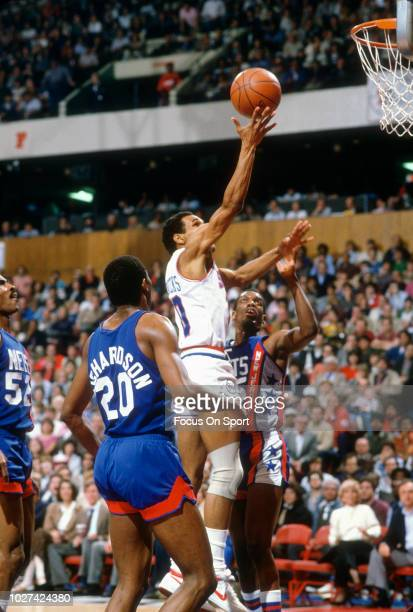 Maurice Cheeks of the Philadelphia 76ers goes in for a layup over Albert King of the New Jersey Nets during an NBA basketball game circa 1983 at The...