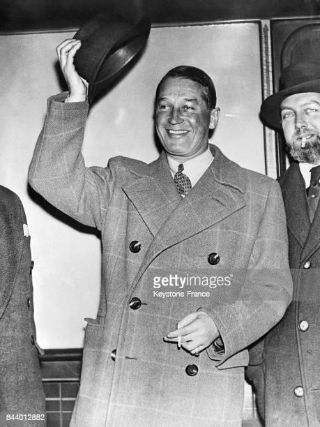 Maurice Chevalier tout sourire salue la foule à son arrivée à Victoria Station à Londres RoyaumeUni le 29 décembre 1935