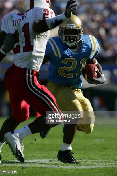 Maurice Drew of the UCLA Bruins attempts to evade OJ Atogwe of the Stanford Cardinal during the game on October 30 2004 at the Rose Bowl in Pasadena...