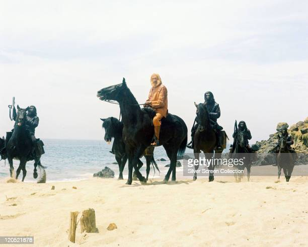 Maurice Evans British actor in costume and wearing an ape mask on horseback with a number of apes also on horseback around him in a publicity still...