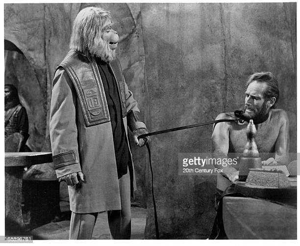 Maurice Evans holds Charlton Heston by a leash in a scene from the film 'Planet Of The Apes' 1968