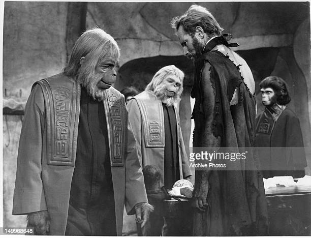 Maurice Evans makes a side remark to Charlton Heston with unidentified council member and Kim Hunter in the background in a scene from the film...