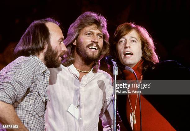 Maurice Gibb Barry Gibb and Robin Gibb of The Bee Gees harmonise at one microphone while performing on stage at the UNICEF A Gift of Song concert...