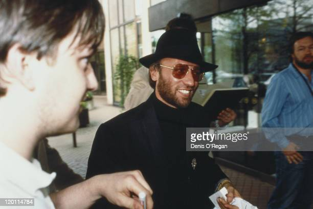 Maurice Gibb of the Bee Gees signs autographs for fans circa 1990