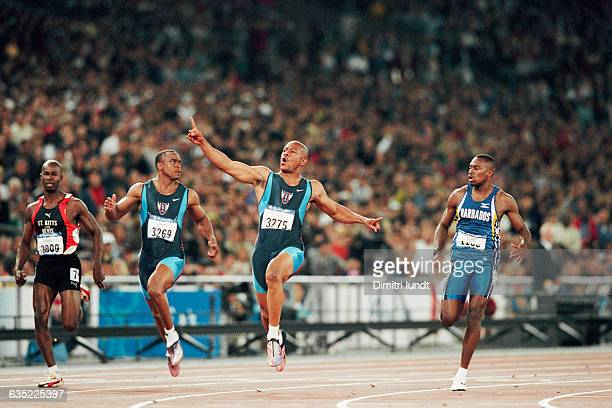 Maurice Greene from the USA celebrates after passing Jonathan Drummond from the USA and Barbados' Obadele Thompson to win the men's 100meter final at...