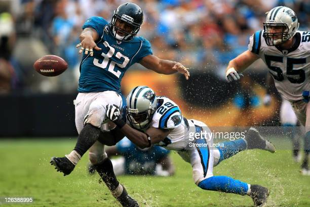 Maurice Jones-Drew of the Jacksonville Jaguars fumbles the ball as he is hit by Jordan Pugh of the Carolina Panthers during their game at Bank of...