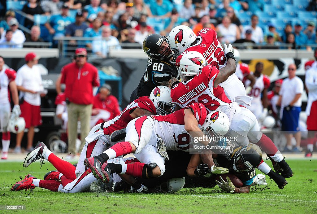 Maurice Jones-Drew #32 of the Jacksonville Jaguars is tackled by Matt Shaughnessy #91 and Daryl Washington #58 of the Arizona Cardinals at EverBank Field on November 17, 2013 in Jacksonville, Florida.