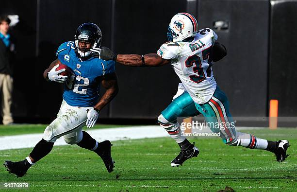 Maurice Jones-Drew of the Jacksonville Jaguars runs the ball against Yeremiah Bell of the Miami Dolphins during the game at Jacksonville Municipal...
