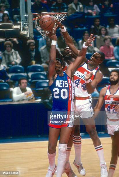 Maurice Lucas of the New Jersey Nets has his shot blocked by Rick Mahorn of the Washington Bullets during an NBA basketball game circa 1980 at the...