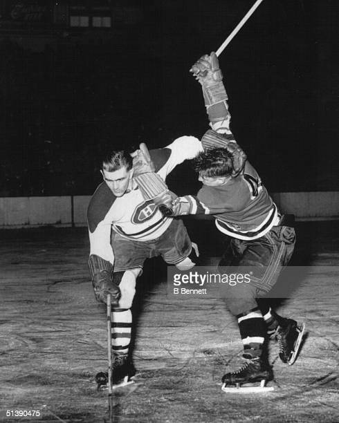 Maurice Richard of the Montreal Canadiens battles for the puck while being checked by an opponent