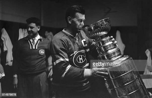"Maurice ""Rocket"" Richard, star of the Montreal Canadiens, gets acquainted with the Stanley Cup here April 20th. The Canadiens won the cup by beating..."