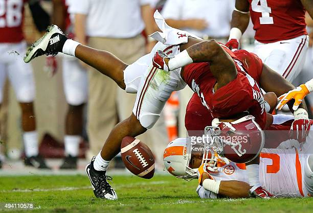 Maurice Smith of the Alabama Crimson Tide attempts to force a fumble as he strips the ball from Josh Malone of the Tennessee Volunteers at...