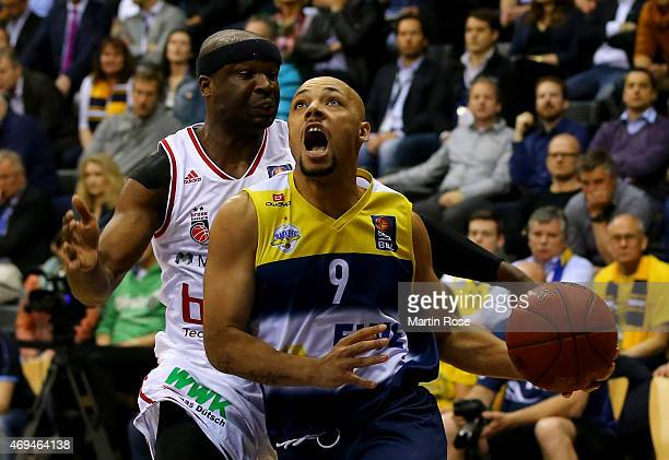 Maurice Stuckey of Oldenburg challenges Dawan Robinson of Bamberg for the ball during the BEKO BBL Top Four final game between EWE Baskets Oldenburg...