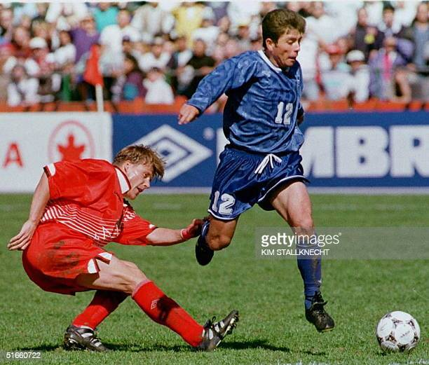 Mauricio Cienfuegos of El Salvador jumps to kick as Geoff Aunger of team Canada slips on the play during first half action of the World Cup...