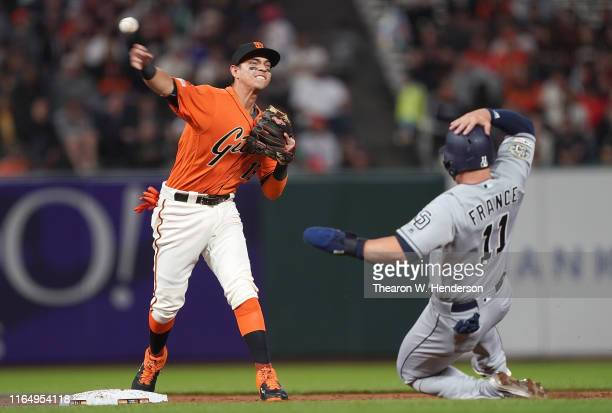 Mauricio Dubon of the San Francisco Giants completes the doubleplay throwing over the top of Ty France of the San Diego Padres in the top of the...