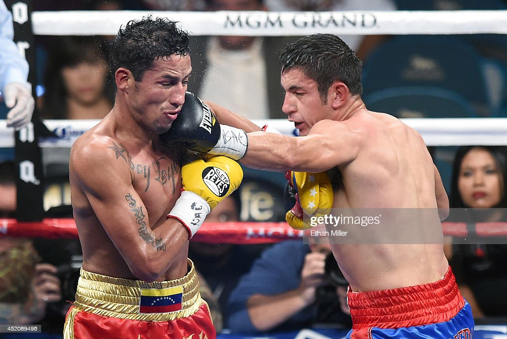 Mauricio Herrera (R) hits Johan Perez in the fifth round of their interim WBA junior welterweight title bout at the MGM Grand Garden Arena on July 12, 2014 in Las Vegas, Nevada. Herrera won Perez's title by majority decision.