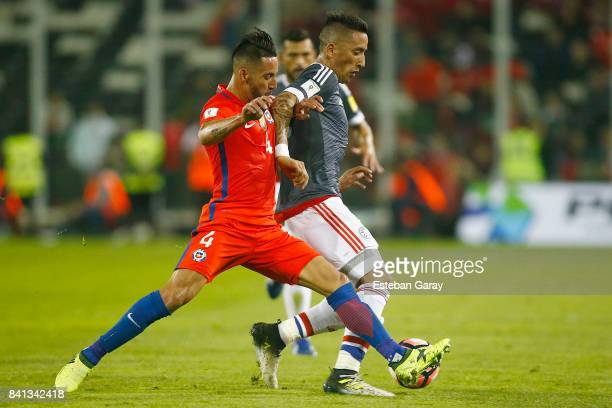 Mauricio Isla of Chile fights for the ball with Lucas Barrios of Paraguay during a match between Chile and Paraguay as part of FIFA 2018 World Cup...