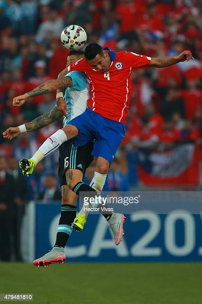 Mauricio Isla of Chile goes for a header with Marcos Rojo of Argentina during the 2015 Copa America Chile Final match between Chile and Argentina at...