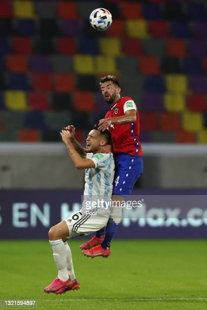 Mauricio Isla of Chile jumps for a header with Lucas Ocampos of Argentina during a match between Argentina and Chile as part of South American...