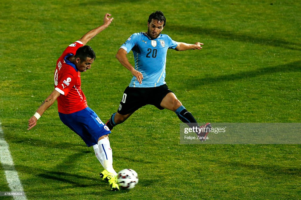 Mauricio Isla of Chile shoots to score the opening goal during the 2015 Copa America Chile quarter final match between Chile and Uruguay at Nacional Stadium on June 24, 2015 in Santiago, Chile.