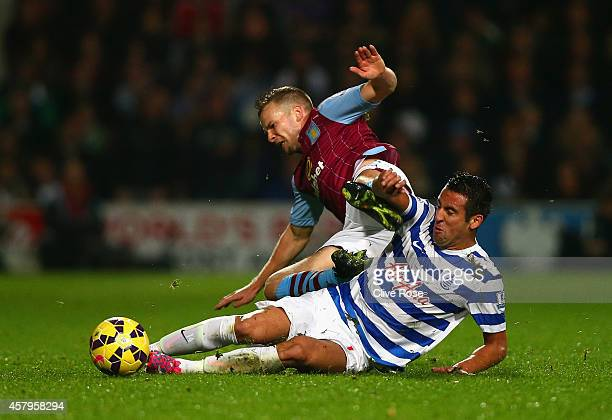Mauricio Isla of QPR slides in to tackle Tom Cleverley of Aston Villa during the Barclays Premier League match between Queens Park Rangers and Aston...