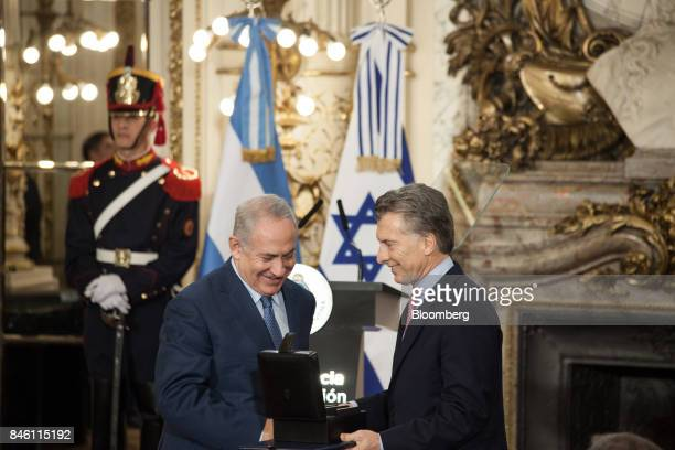 Mauricio Macri Argentina's president right presents Benjamin Netanyahu Israeli's prime minister with external hard drives containing information on...