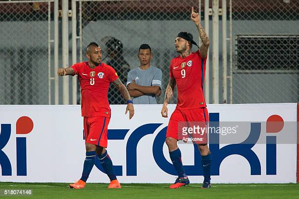 Mauricio Pinilla of Chile celebrates with Arturo Vidal after scoring the first goal of his team during a match between Venezuela and Chile as part of...