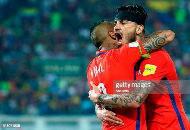 Mauricio Pinilla of Chile celebrates with teammate Arturo Vidal after scoring second goal of his team during a match between Venezuela and Chile as...